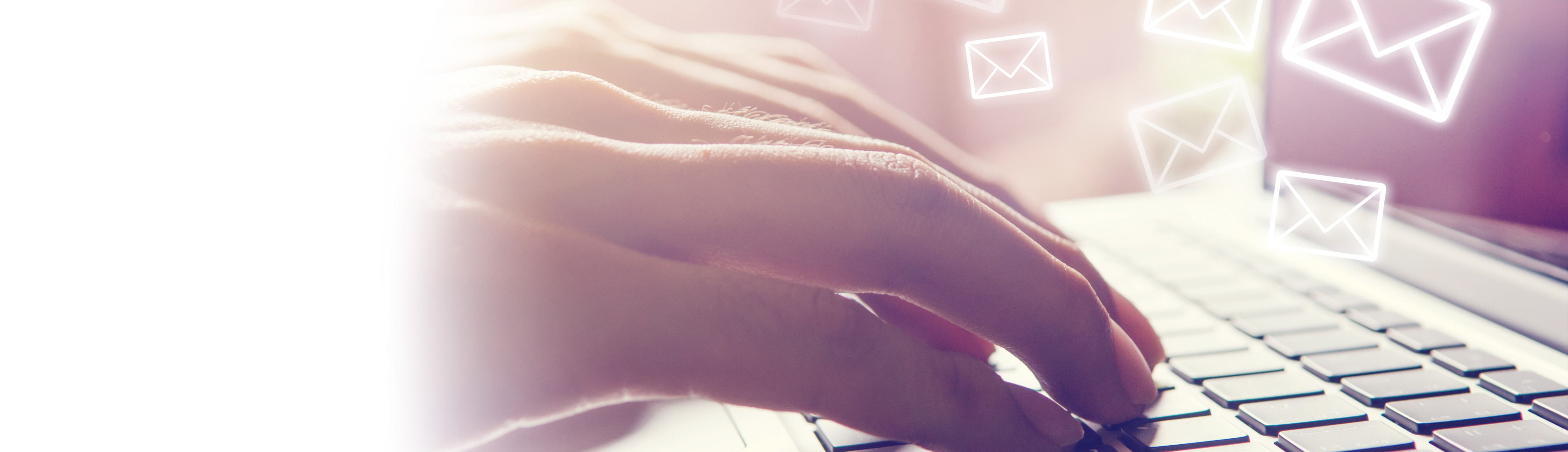 Hands on a keyboard, e-mail icons flying out from the screen.